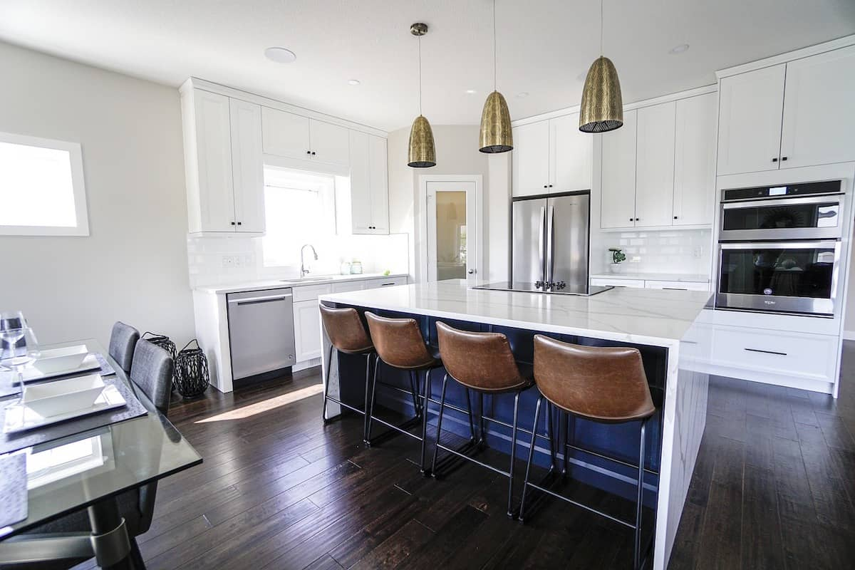 Photo of white kitchen cabinets, and white marble island countertop.
